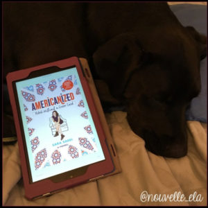 A dog lying down with a kindle beside it, displaying the cover of the book Americanized by Sara Saedi
