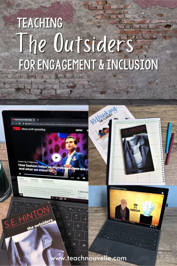 """Two laptops, books, notebooks, and pins on a table in front of a brick wall with the text """"Teaching The Outsiders For Engagement & Inclusion"""""""