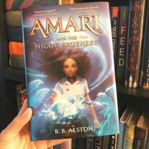 The book Amari and the Night Brothers by B.B. Alston held up in front of a book shelf.