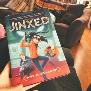 The book Jinxed by Amy McCullock help up in front of a living room