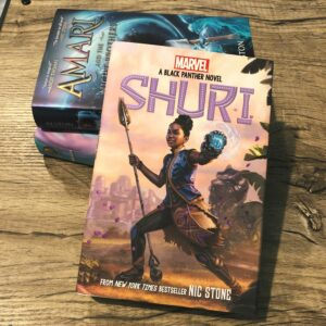 A bookstack on a woodgrain background, the book on top is Shuri by Nic Stone.