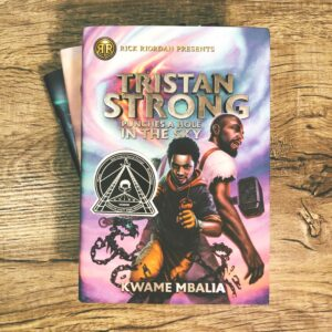 A woodgrain background and the book Tristan Strong Punches a Hole in the Sky by Kwame Mbalia